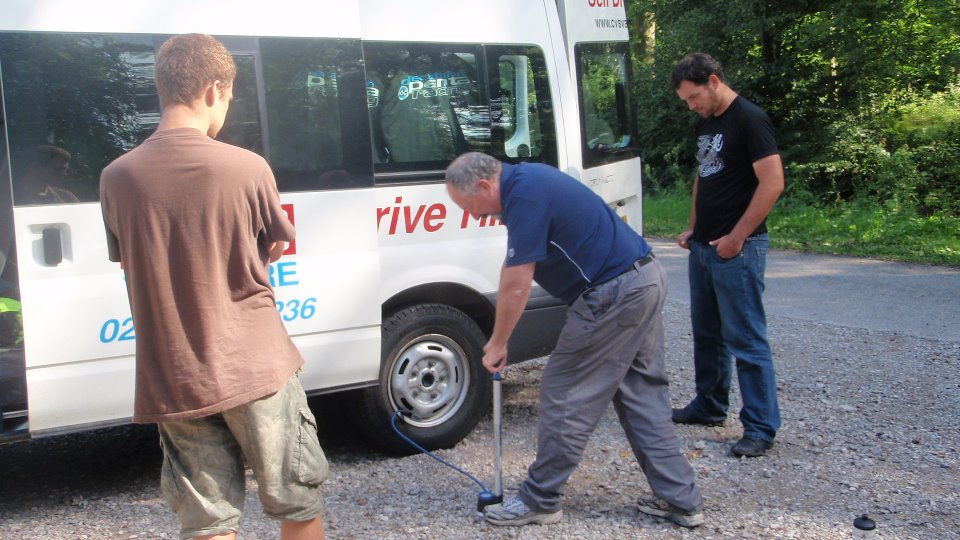Matt and Simon supervise Clive pumping up the minibus tyre